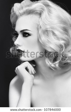 Black and white profile portrait of young beautiful woman with blond curly hair - stock photo