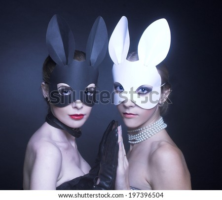Black and white rabbits. Two young women in masks. - stock photo