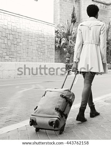 Black and white rear view of elegant professional woman walking in a classic city street dragging a luggage suitcase, outdoors. Tourist holiday with bag in destination town exterior, lifestyle. - stock photo