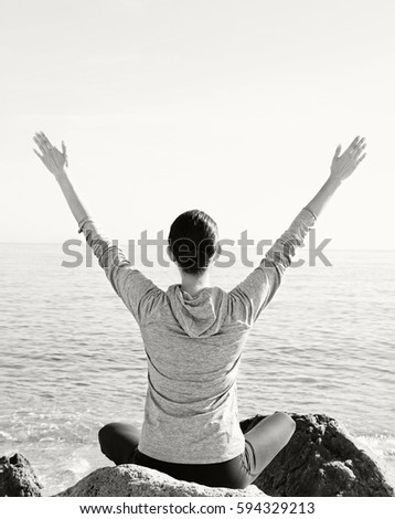 Black and white rear view of healthy mature woman sitting in yoga position on beach, meditating contemplating the sea with arms outstretched, outdoors. Fitness sport activities, well being lifestyle.