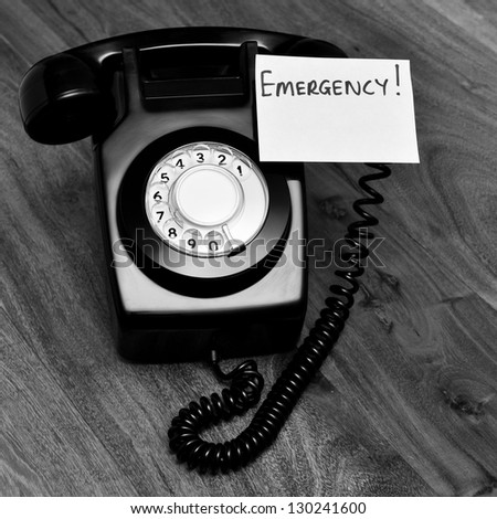 Black and white retro phone with emergency note - stock photo