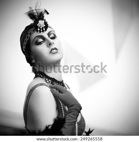 Black-and-white retro style depiction of a woman in typical style of the 1920s or 1930s. She's fashionably adorned in black lace, pearls, evening gloves and a pearl-accented wrap-around headpiece. - stock photo