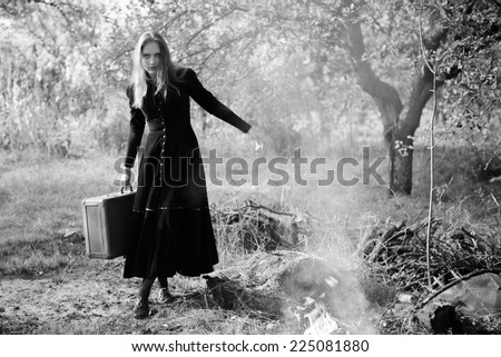 Black and white retro style image of lonely woman with suitcase walking among smokes and ashes in long vintage coat - stock photo