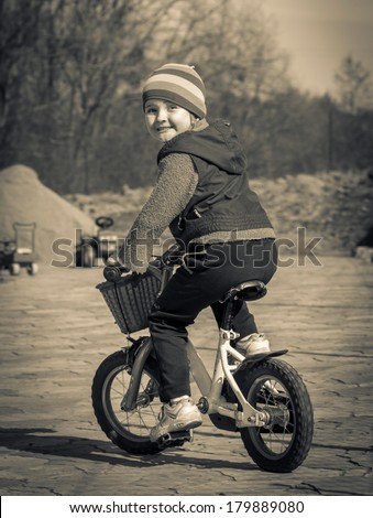 black and white retro style photo of child riding a bike - stock photo