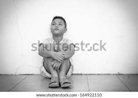 Black and white, Sad boy sitting on the floor by the wall - stock photo