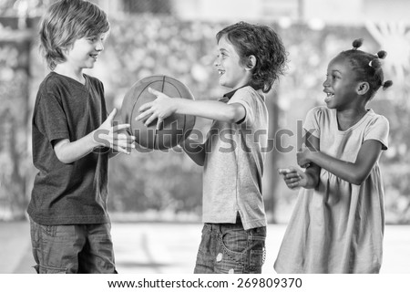 Black and white scene of children playing basketball at school. - stock photo