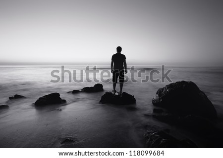 black and white seascape with alone man on the rocks - stock photo