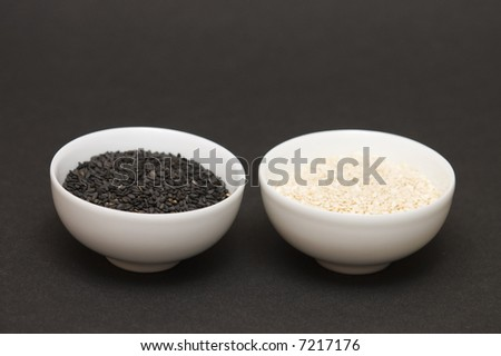 black and white sesame seeds in a bowls on dark background - stock photo