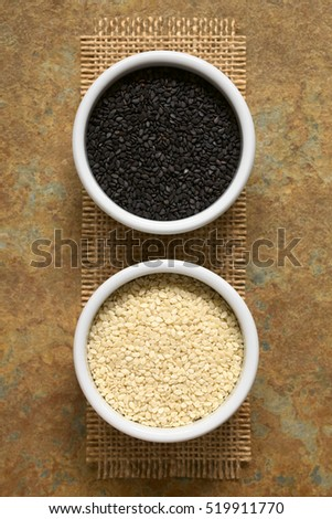 Black and white sesame seeds in small bowls, photographed overhead with natural light (Selective Focus, Focus on the seeds on the top)