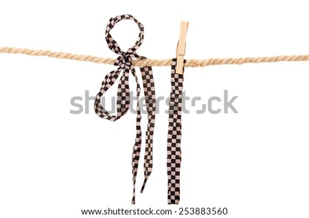 black and white shoelaces hanging on a rope clothesline isolated on white - stock photo