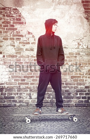 black and white shoot of a teenage boy with hoodie standing on a long board - stock photo