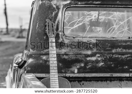 Black and white shot of an old acoustic guitar in the bed of an old rusted truck with bullet holes in the windshield in Clarksdale, Mississippi.