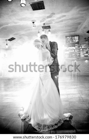 Black and white shot of bride and groom kissing passionately during first dance - stock photo