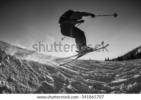black and white shot of free skier jumping off a kicker