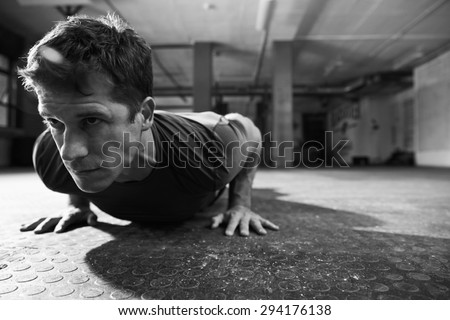 Black And White Shot Of Man In Gym Doing Press-Ups - stock photo