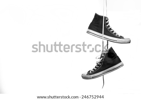 Black and white shot of pair of sneakers hanging in front of a white background - stock photo