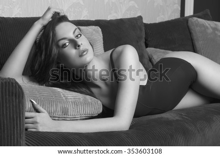black and white shot of very sexy brunette female with perfect slim body and black lingerie, in sensual pose on velvet sofa  - stock photo