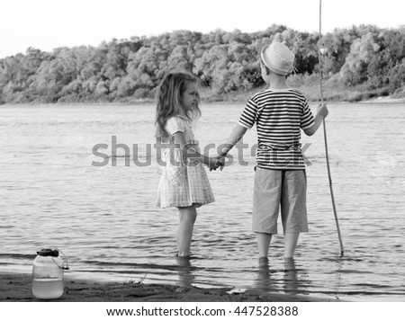 black and white shot of vintage style amusing boy and girl on the river summer day - stock photo