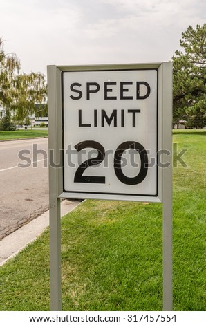 Black and white sign for 20 mph speed limit - stock photo