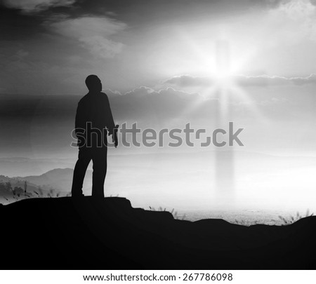 Black and white silhouette human standing over blurred the cross on nature background. - stock photo