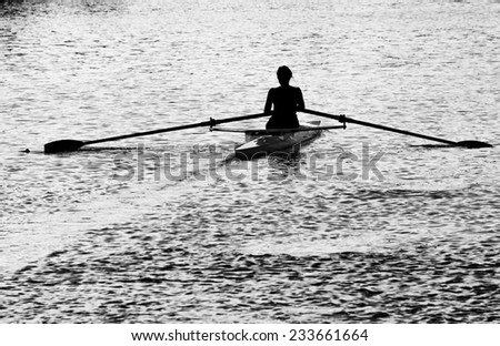Black and white silhouette of an unrecognizable female rower on a river at dusk. - stock photo