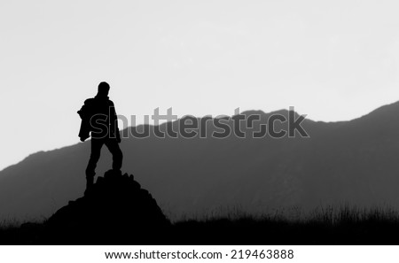 Black and white silhouette of hiker on the top of the hill  - stock photo