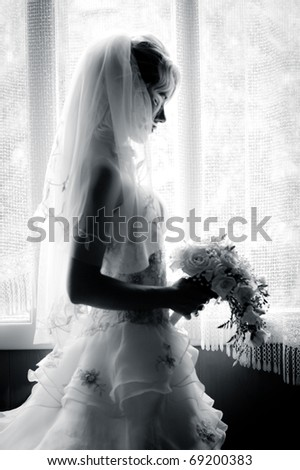 black and white silhouette of the bride weared in dress and veil with a bouquet - stock photo