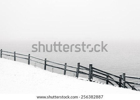 black and white snowy scene with a snow covered hillside and a fence running downward from left to right. lake in the background