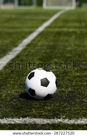 Black and white soccer ball on green soccer pitch. - stock photo