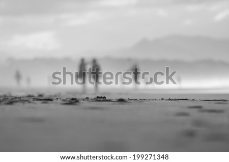 Black and White. soft focus people walking on beach 1 - stock photo