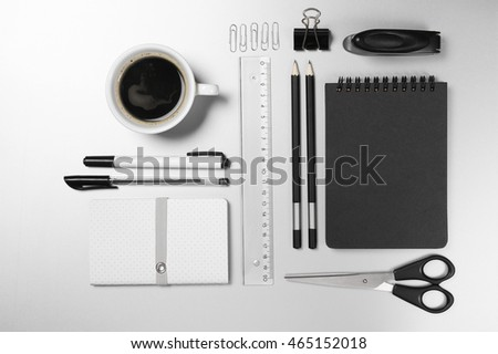 Black and white stationery on gray desk: notepads, pencils, scissors, stapler, clip, pins, ruler, pens, cup of coffee. Top view point.