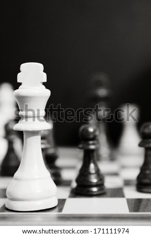 Black and white still life close up detail view of a king chess wooden piece on a chess board while a strategic game is being played. Professional game playing. - stock photo