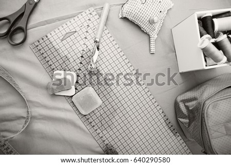 Black and white still life of a home sewing work desk with seamstress and tailor tools, home interior. Working trades and skills. Fashion design college studying and learning, recreation lifestyle.