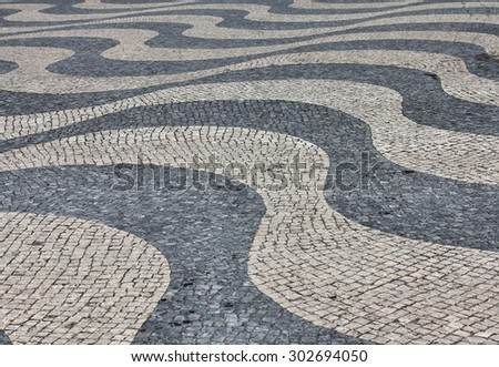 Black and white stone pavement mosaic in Lisbon, Portugal