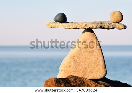 Black and white stones in balance at seashore - stock photo