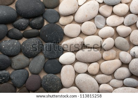 Black and white stones lie side by side on the sand - stock photo