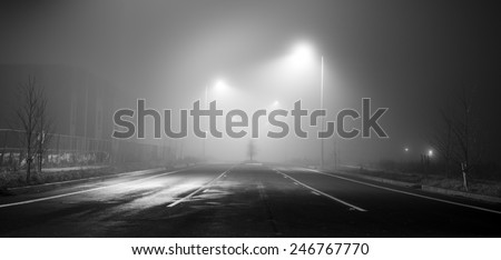 Black and white street at night with heavy fog - stock photo