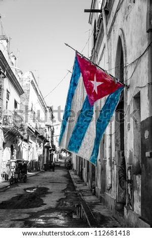 Black and white street scene in Old Havana with a colorful cuban flag - stock photo
