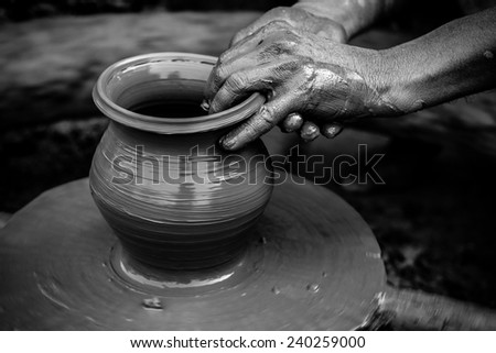 Black and white striking image of a potter's hands shaping soft clay to make an earthen pot - stock photo
