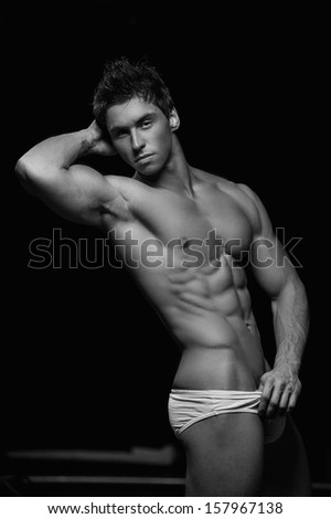black and white strong man in the underwear showing his muscles - stock photo