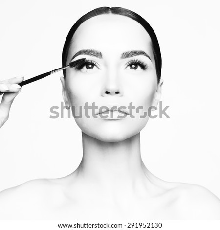 Black and white studio fashion photo of beautiful young lady applied mascara.  Beauty and care. Extension eyelashes. Spa salon. Perfect face makeup - stock photo