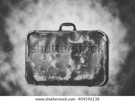 black and white studio image of an old fashioned retro leather travel suitcase - stock photo