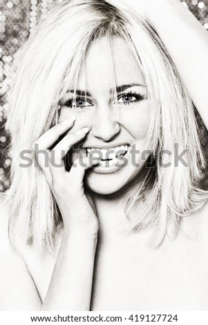 Black and white studio photograph of a stunningly beautiful young blonde woman biting her finger and smiling