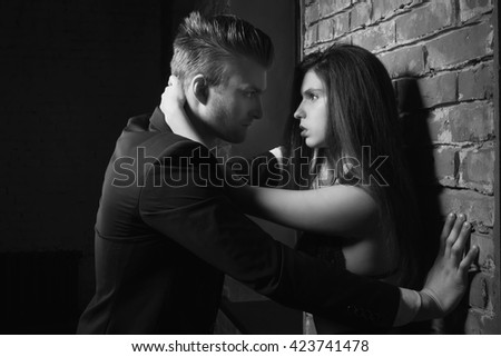 Black and white Studio photos erotic young couple. Girl in a dress, man in a business suit - stock photo