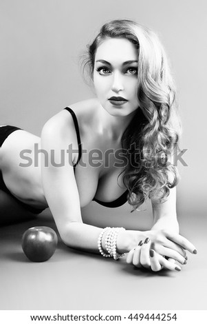 Black and white studio portrait of beautiful young woman with apple. - stock photo