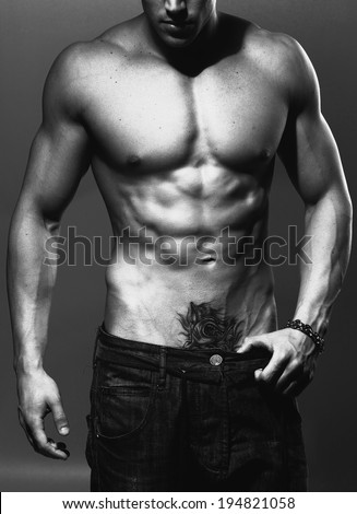 black and white studio shoot of strong athletic man on grey background close up