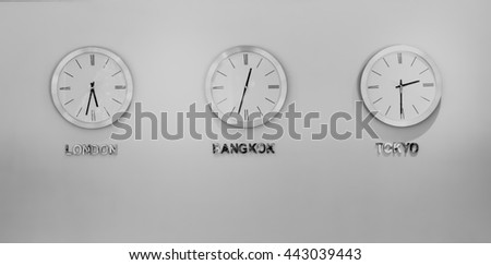 Black and white three timezone Circle watch hanging on wall