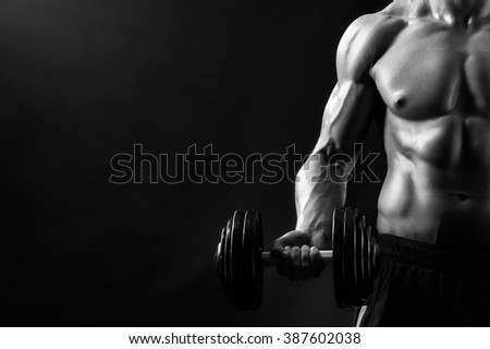 Black and white, True hard worker. Cropped closeup of a strong muscular male holding a dumbbell posing against black background