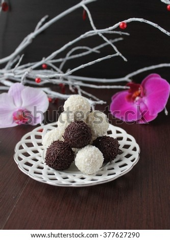 black and white truffles of chocolate and coconut topping. Homemade candy. - stock photo