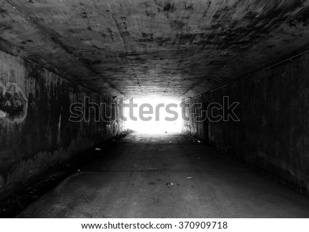 Black and white tunnal with bright light at the exit